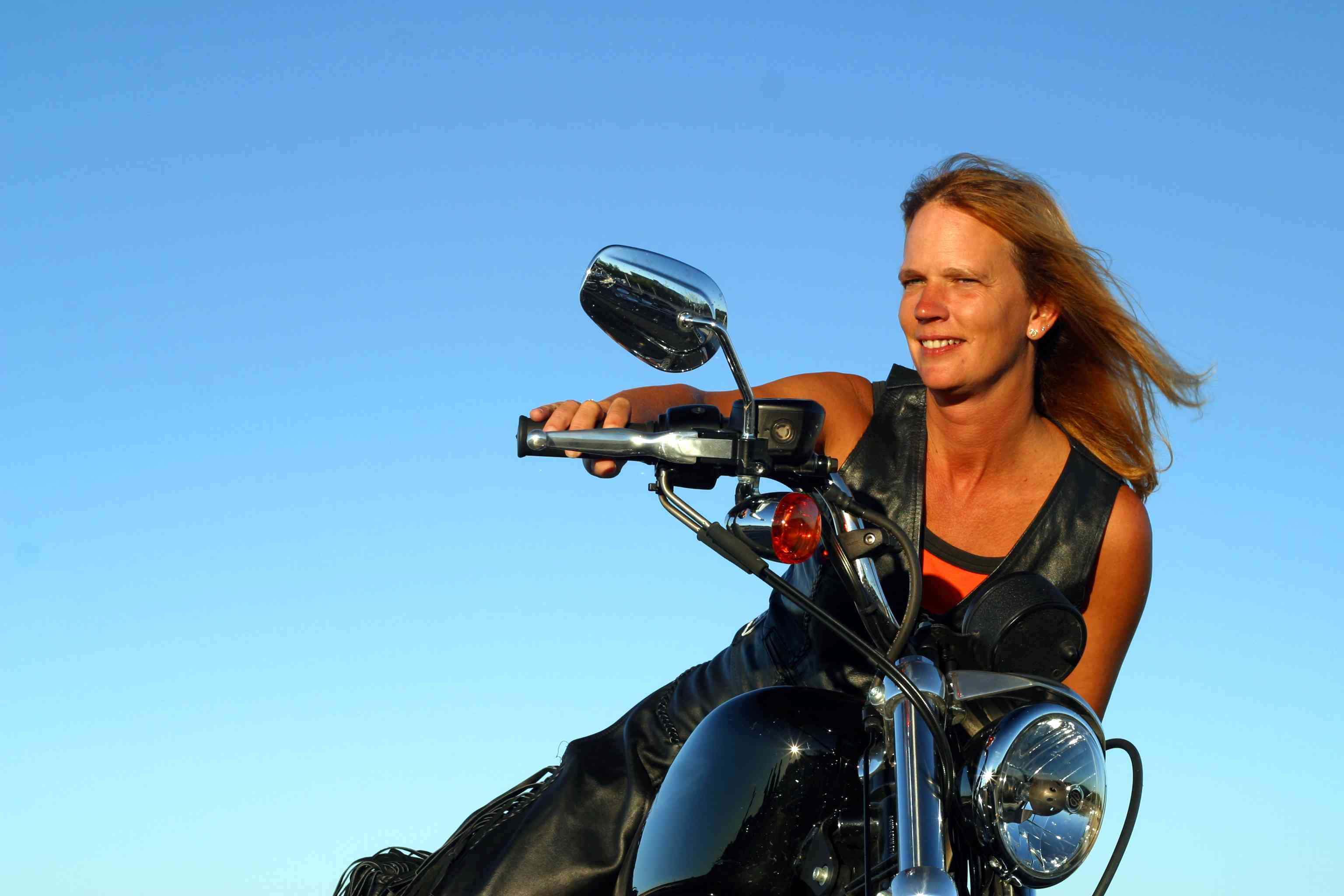 Woman on motorcycle with clear skies