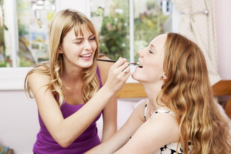 Teenage girl applying makeup to younger sister