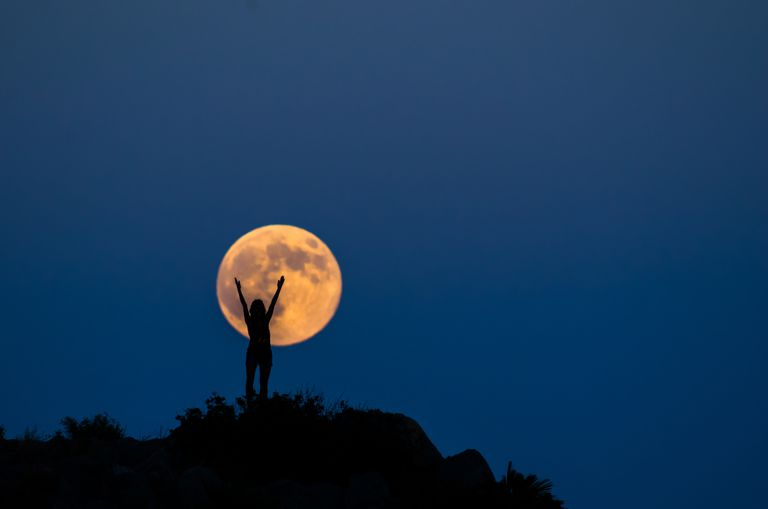 Woman silhouette on the full moon