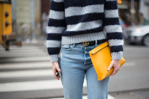 Close up of street style woman in striped sweater and jeans and yellow purse