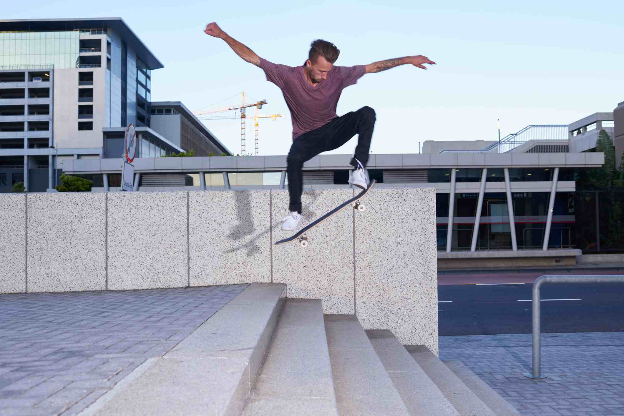 Shot of a young man skating down a flight of stairs