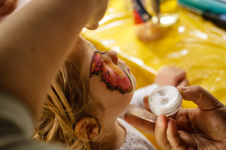 Painting a young child's face, emphasis on glitter paint.