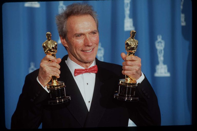 Clint Eastwood holding dual Oscars at the Academy Awards.