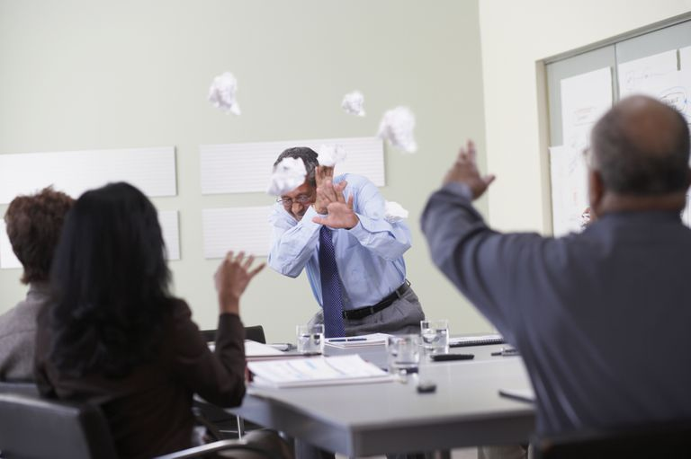 Businesspeople throwing paper balls