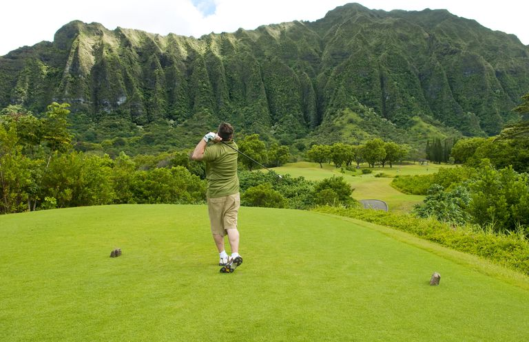 Hawaii, Oahu, Honolulu, Ko'olau Golf Course, Man driving on the 5th hole with beautiful mountain view.