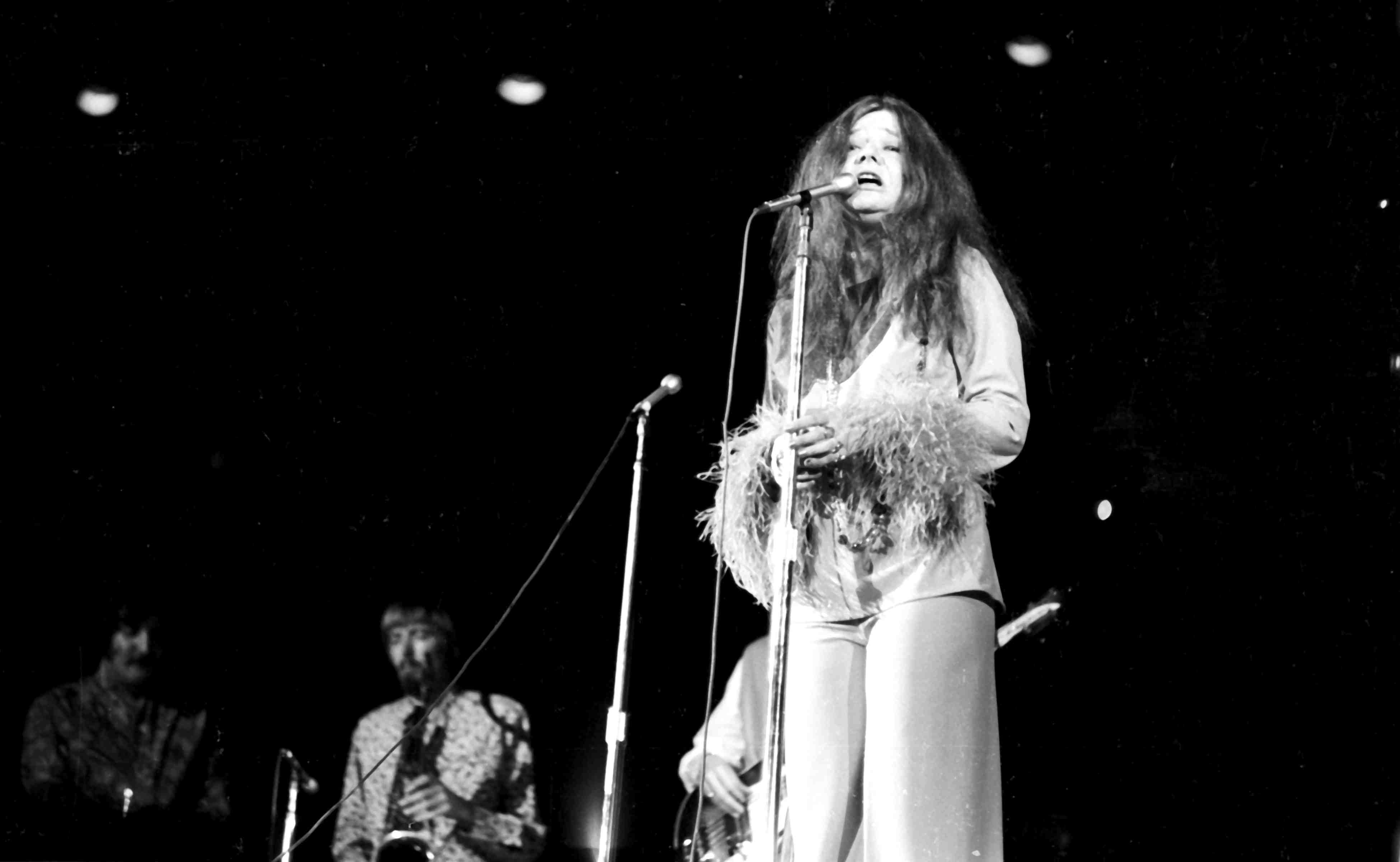 Janis Joplin performs live on stage, black and white photograph.
