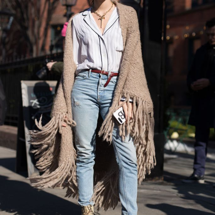 Woman in jeans and fringed shawl