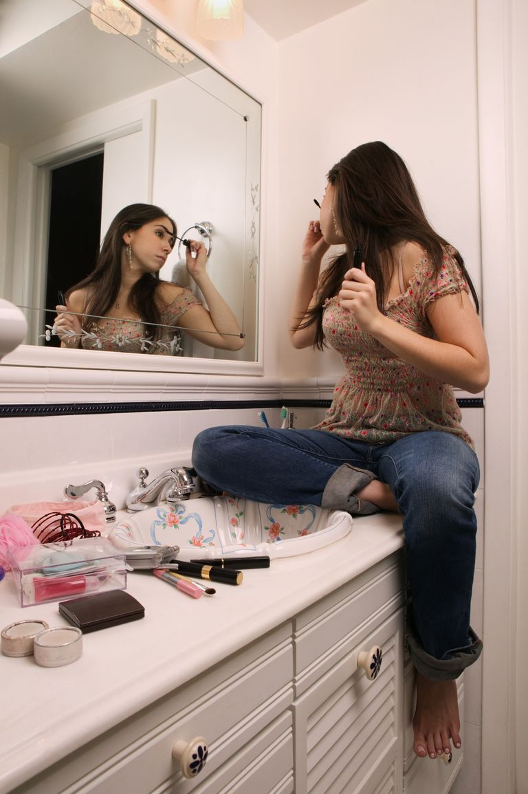 Teen girl sitting on her counter doing her makeup