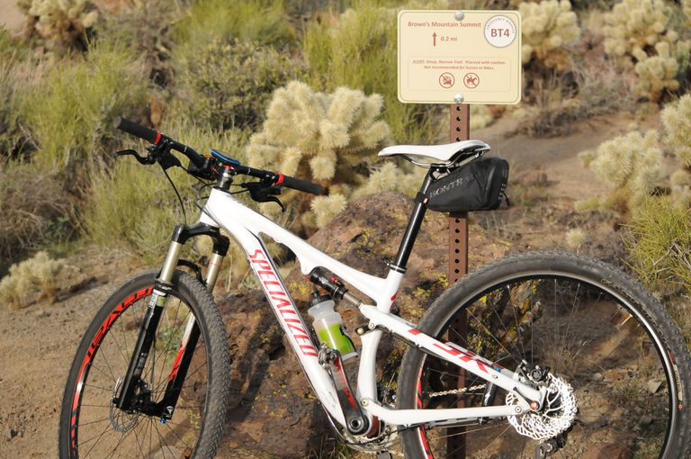 mountain bike leaning against trail sign