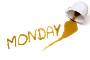 Spilt cup of coffee with the word Monday spelled out in coffee