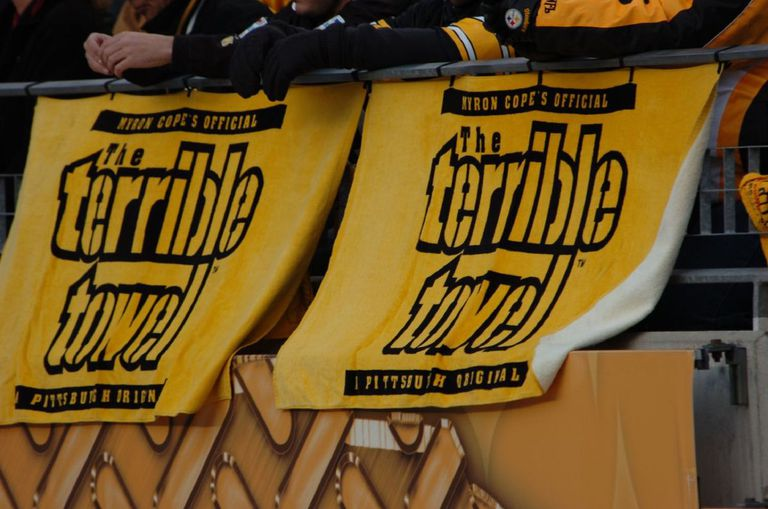 Fans holding The Terrible Towel at a Pittsburgh Steelers football game