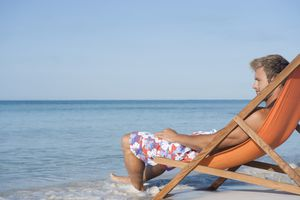 Young man reclining in deckchair looking at ocean, side view