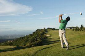 Golfer tees off, viewed from behind