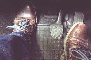 Low Section Of Man Wearing Shoes On Pedals In Car