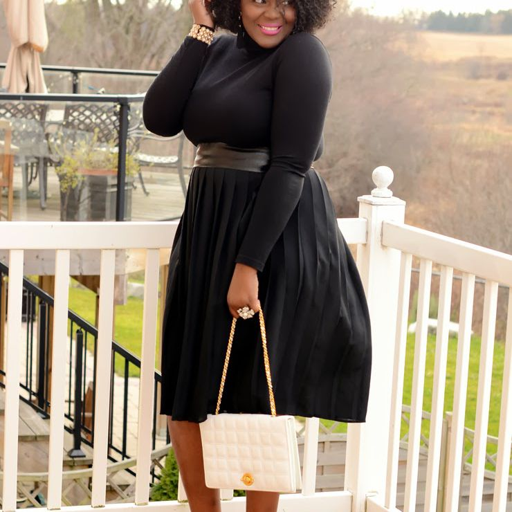 Woman in black dress with a white purse