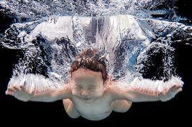 Portrait of baby swimming underwater in pool