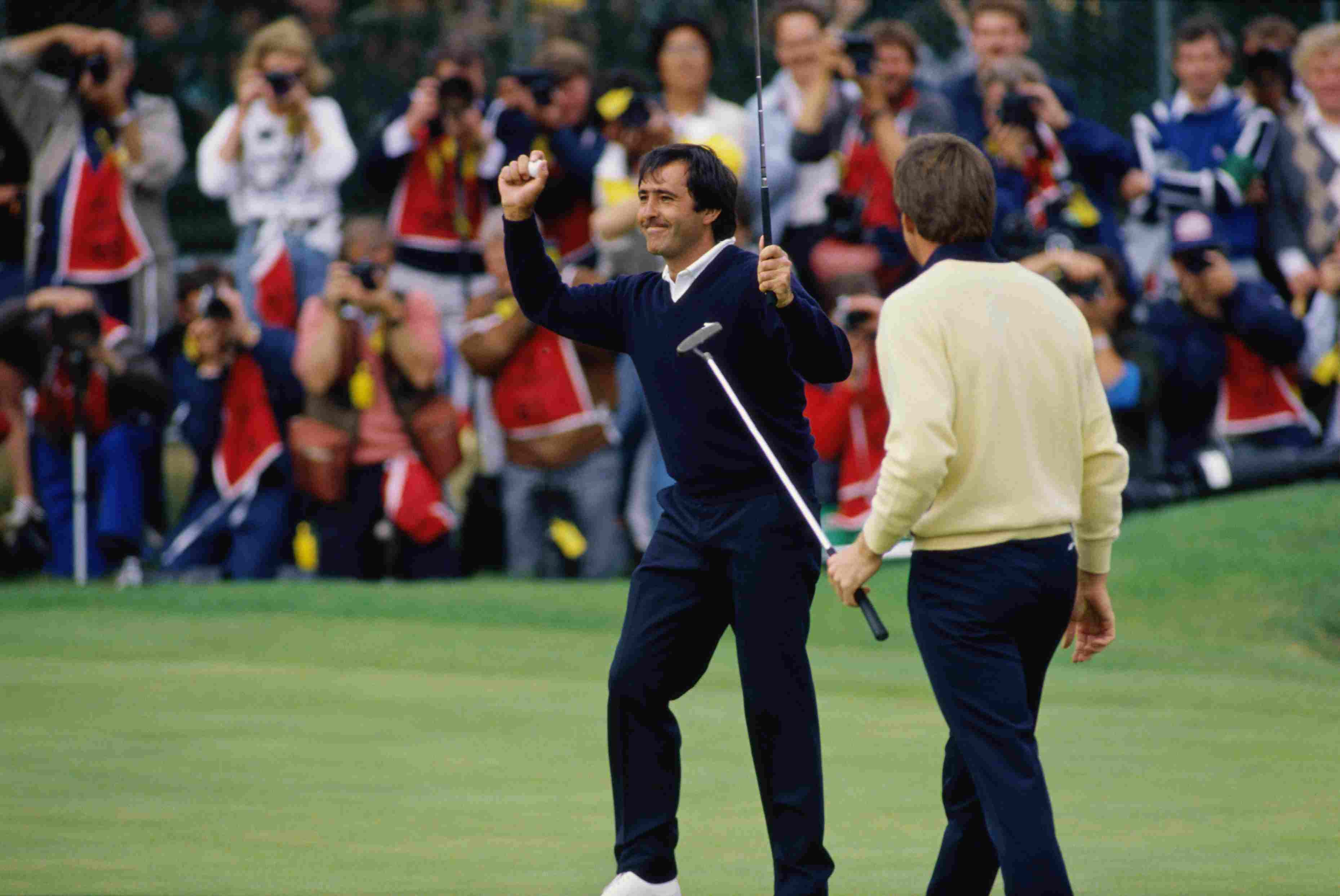 Nick Price of Zimbabwe looks on as Spanish golfer Severiano Ballesteros (left) celebrates his final putt on the 18th green during the Open Championship at the Royal Lytham and St Annes Golf Club, July 1988