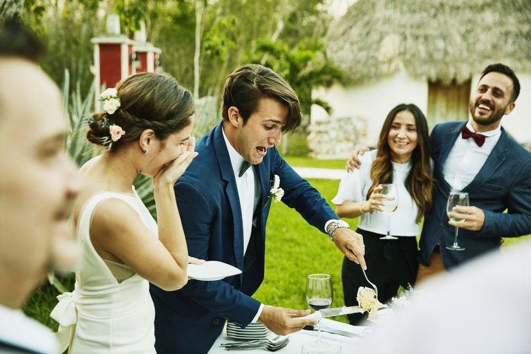 Laughing bride and groom cutting cake during outdoor wedding reception