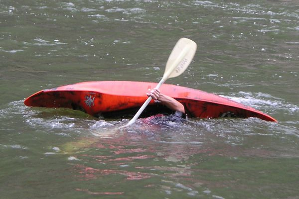 A man rolling a kayak is underwater but about to break the surface