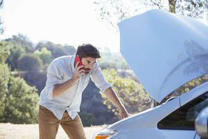 Man talking on cell phone and checking car engine at roadside