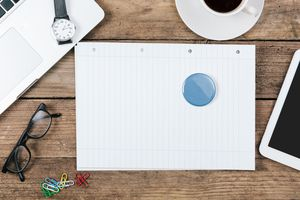 Paperweight On Blank Page Surrounded By Office Supplies On Table
