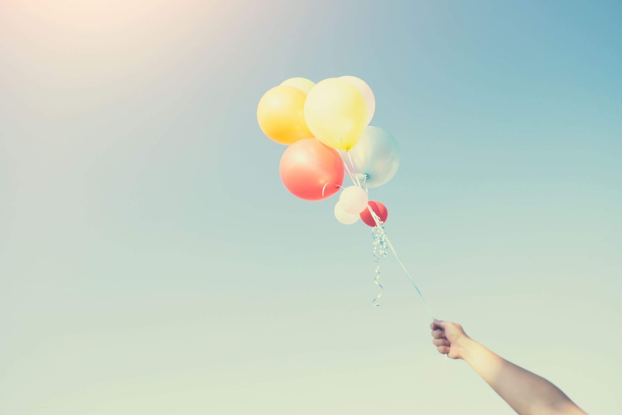 Person Letting Go of Balloons, Symbolizing Letting Go of Worries