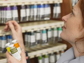 Woman selecting tubes of paint in art shop, profile