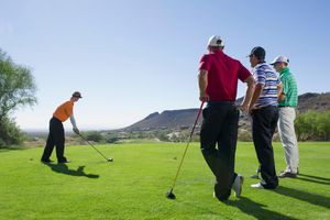 Man playing golf with friends watching