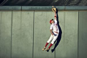 USA, California, San Bernardino, baseball player making leaping catch at wall