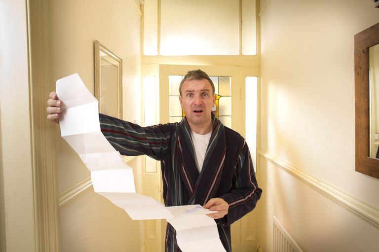 Man holding a large bill.