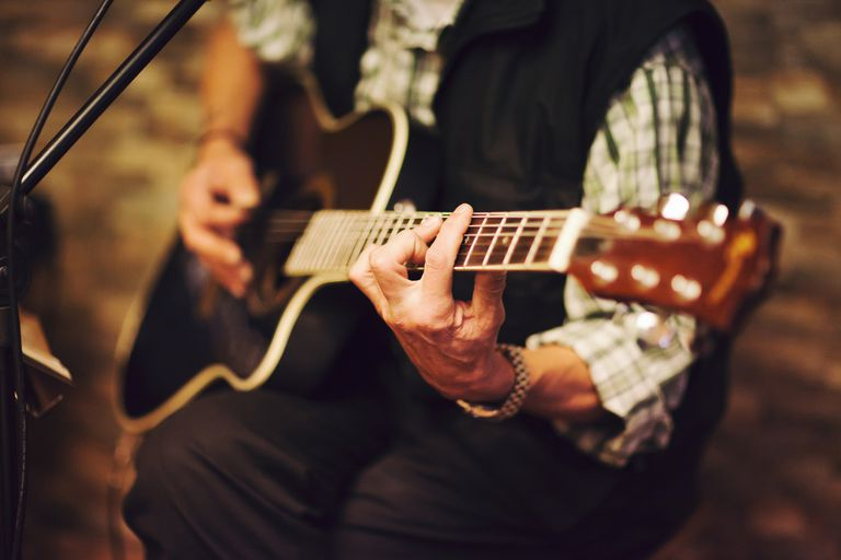 midsection of person playing acoustic guitar