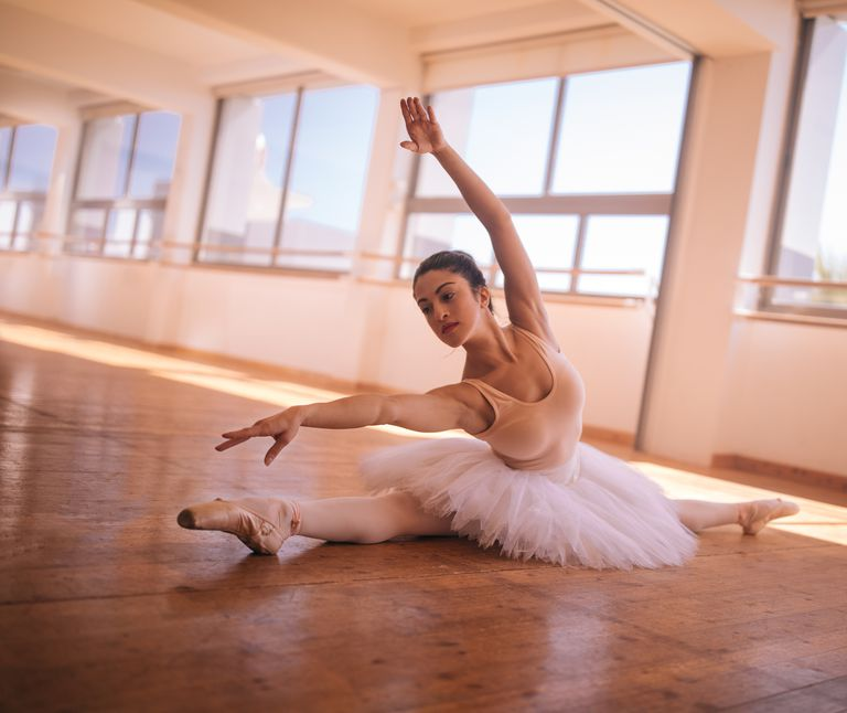Flexible ballerina doing a side split during ballet session