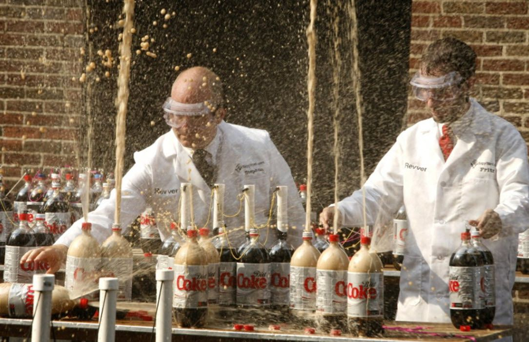 Two scientists demonstrating what happens when you put Mentos candy in Diet Coke.