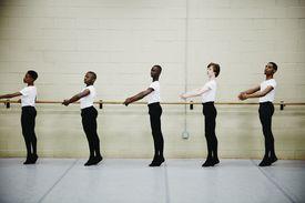 Male ballet dancers practicing at barre in studio