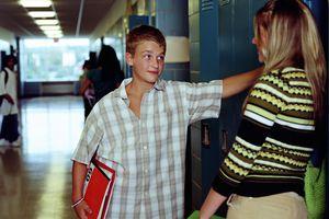 Teenagers (13-15) talking in high school hallway, near lockers