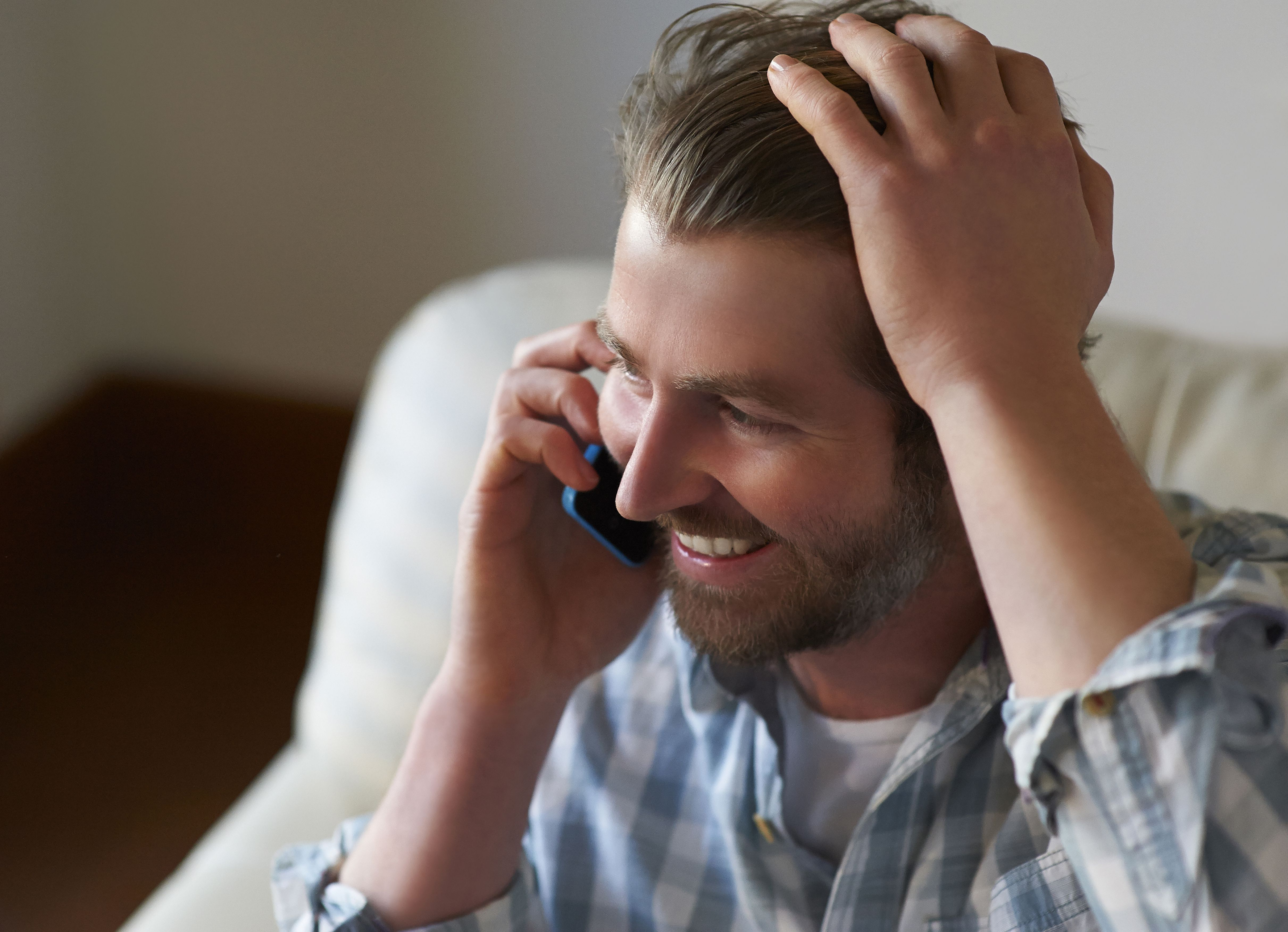 Man using mobile phone at home.