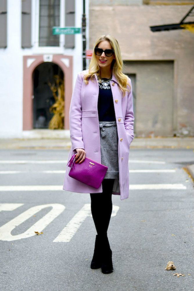 Woman in purple coat and black sweater and grey skirt
