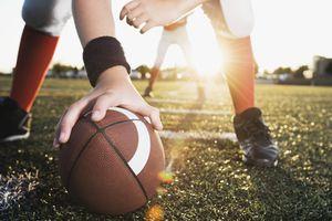 Close up of football center preparing to snap football