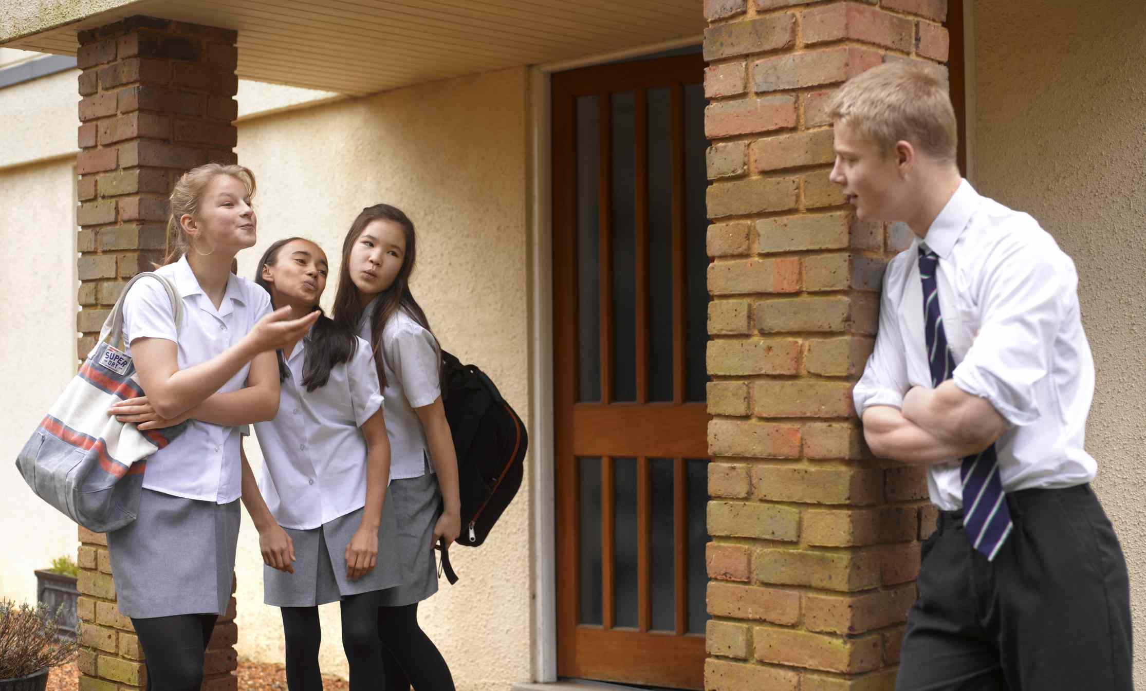 School girls blowing kisses to school boy