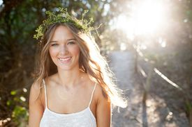 Woman with flower crown walking along dirt path.