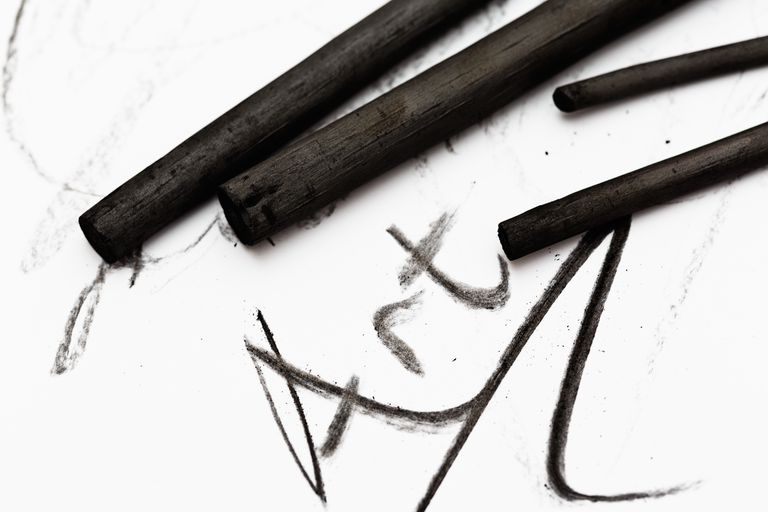 Sticks of charcoal write Art on white sketchpad