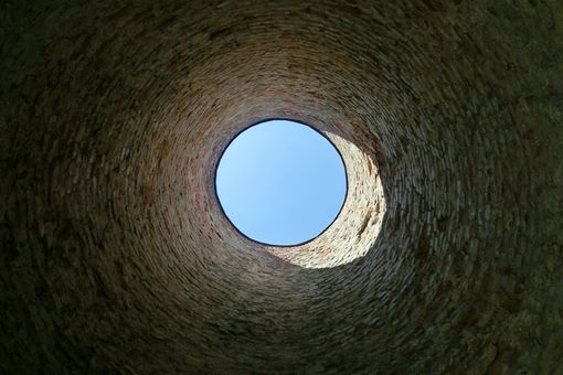 Directly below shot of sky seen through well