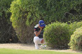 Golfer Rafa Cabrera-Bello ponders an unplayable ball that is under a bush.