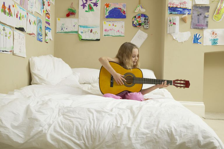 Girl (5-7) sitting on bed playing acoustic guitar