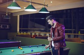 Man in a leather jacket playing pool.