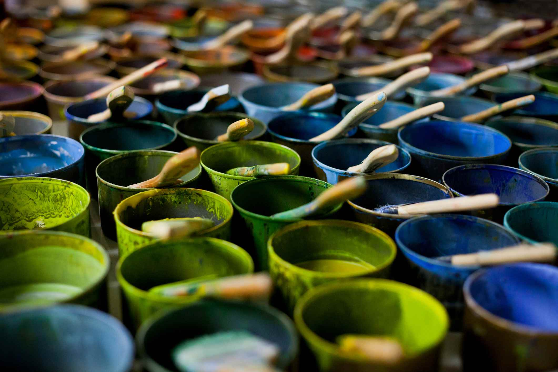 Colorful, small cans of paint with brushes in them