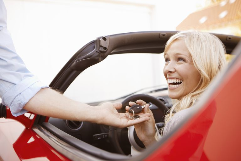 Woman receiving keys to an electric car