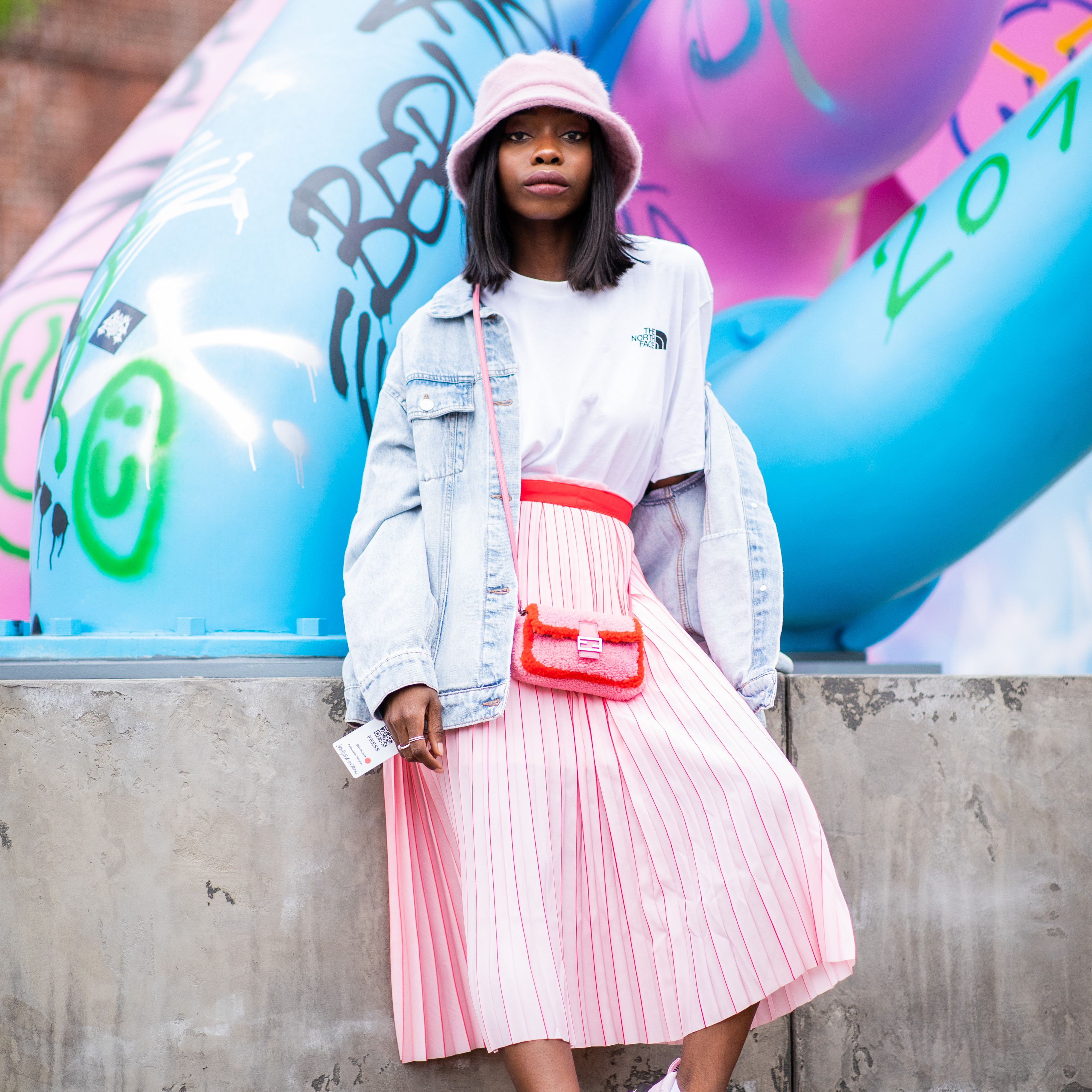 Street style fashion woman in jean jacket and pleated pink maxi skirt