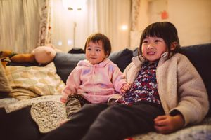 Lovely little sibling enjoying movie at home joyfully.