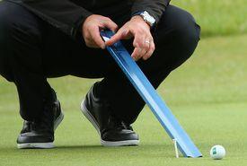 Tournament official rolls golf ball down Stimpmeter to measure the green speeds